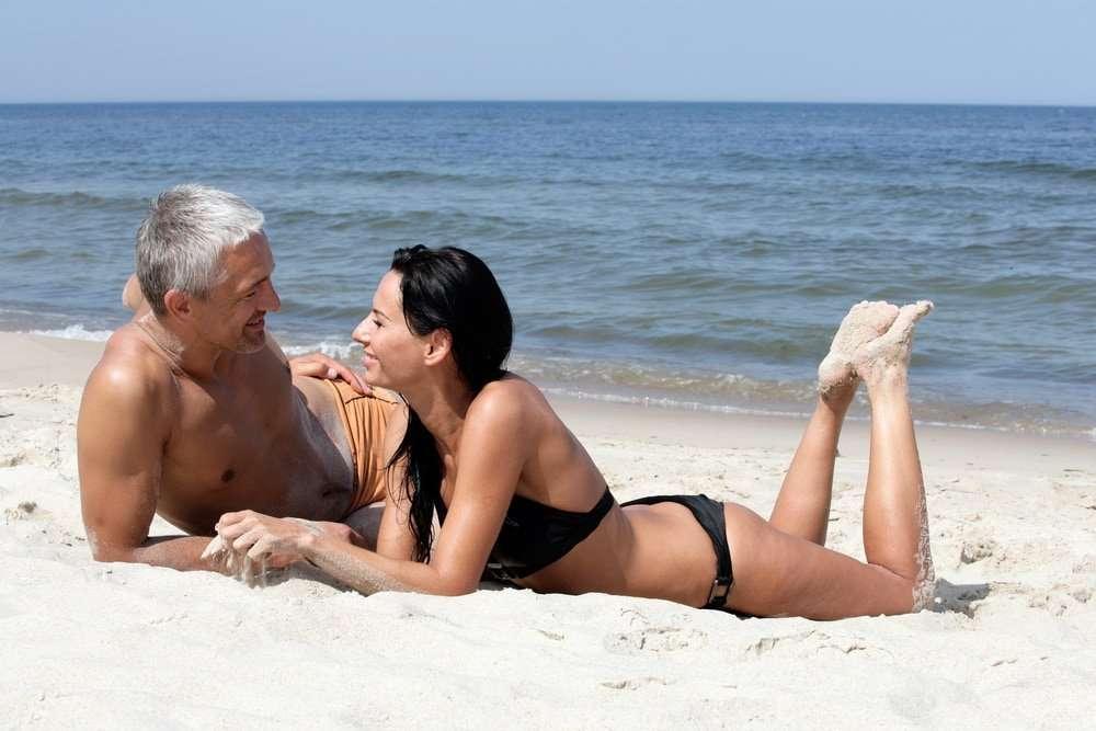 older couple on a beach flirting